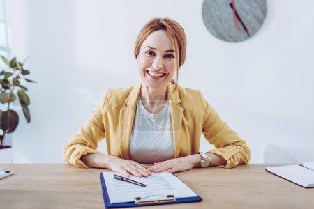 Photo pour Heureux recruteur en veste jaune assis près du presse-papiers et stylo - image libre de droit