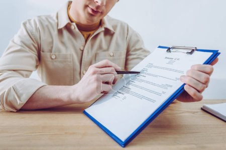 Photo for Cropped view of recruiter pointing at clipboard with pen - Royalty Free Image