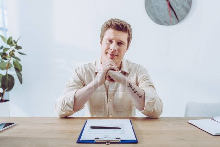 Photo for Cheerful and handsome man sitting with clenched hands near clipboard and pen - Royalty Free Image