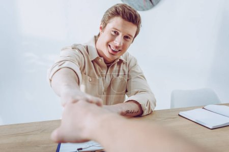 Photo for Cheerful and handsome recruiter giving fist bump to employee - Royalty Free Image