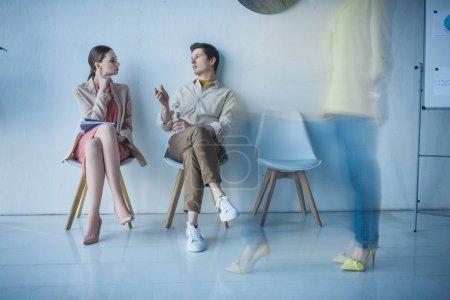Photo pour Employé beau avec la bouteille de l'eau s'asseyant et parlant avec la femme attirante - image libre de droit