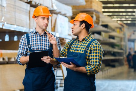 Photo for Two serious multicultural warehouse workers talking and holding clipboards - Royalty Free Image