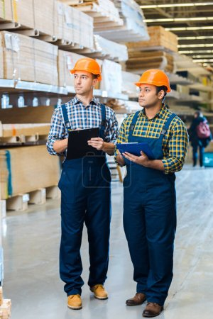 two attentive multicultural warehouse workers in uniform writing in clipboards