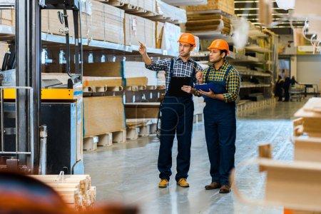 Photo pour Travailleur d'entrepôt sérieux en uniforme pointant du doigt tout en se tenant près de collègue indien - image libre de droit