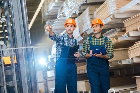 deux travailleurs multiculturels en chemises à carreaux et vasques de sécurité tenant des presse-papiers
