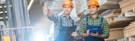 Photo for Panoramic shot of warehouse worker pointing with finger while standing near indian friend - Royalty Free Image