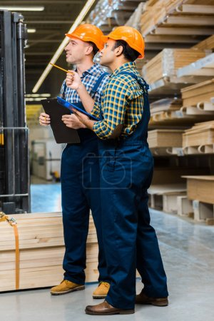 Photo pour Two multicultural workers in uniform holding clipboards while standing in warehouse - image libre de droit