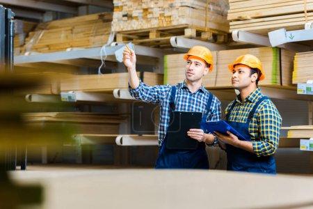 Photo pour Foyer sélectif de deux travailleurs multiculturels entrepôt avec presse-papiers debout dans l'entrepôt - image libre de droit