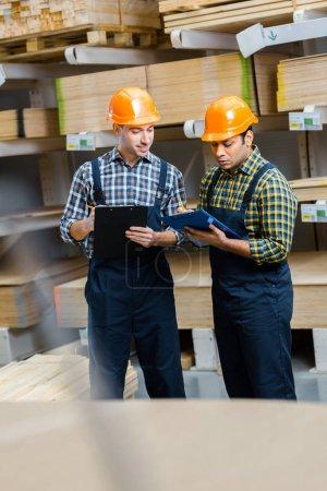 Foto de Enfoque selectivo de dos trabajadores de almacén multiculturales en escritura uniforme en portapapeles - Imagen libre de derechos