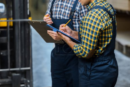 Photo for Partial view of two multicultural warehouse workers in plaid shirts writing in clipboards - Royalty Free Image