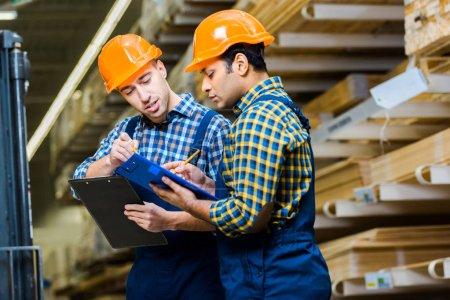 Photo pour Deux travailleurs multiculturels attentifs en uniforme et des casques qui écrivent dans les presse-papiers - image libre de droit