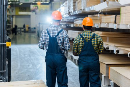 Photo for Back view of two multicultural workers in overalls, plaid shirts and helmets in warehouse - Royalty Free Image