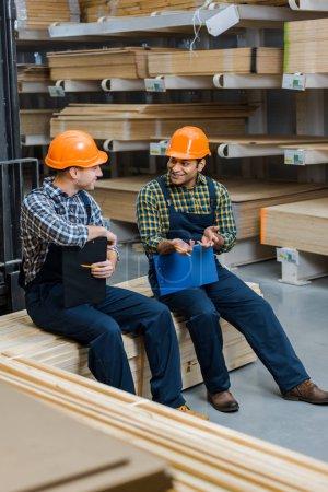 Photo pour Deux travailleurs multiculturels souriants avec des planchettes parlant tout en étant assis dans l'entrepôt - image libre de droit