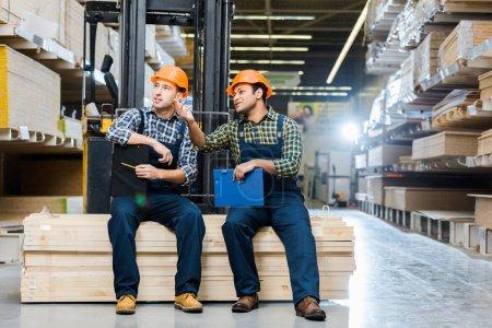 Photo pour Deux travailleurs multiculturels parlant assis sur du contreplaqué dans un entrepôt - image libre de droit