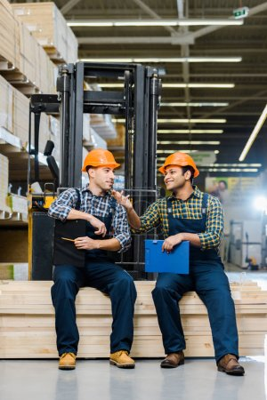 Photo for Two smiling multicultural workers with clipboards talking while sitting on plywood - Royalty Free Image