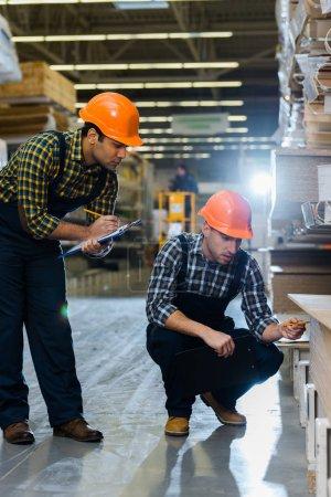 Foto de Dos colegas multiculturales en uniformes y cascos que trabajan en almacén - Imagen libre de derechos