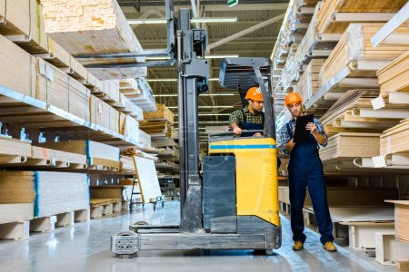 Photo for Warehouse worker writing in clipboard near indian colleague sitting in forklift machine - Royalty Free Image