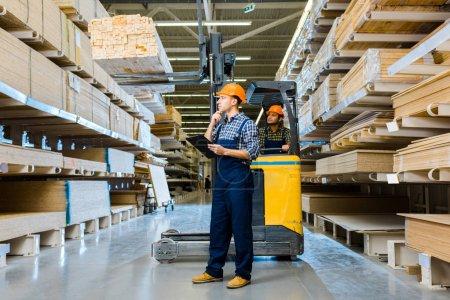Foto de Trabajador de almacén indio sentado en la máquina de montacargas cerca de colega reflexivo con portapapeles - Imagen libre de derechos