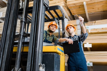 Photo for Warehouse worker pointing with pencil near indian colleague sitting in forklift machine - Royalty Free Image