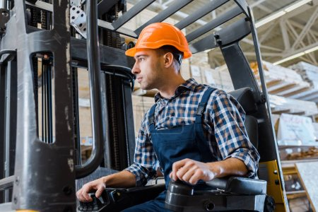 Photo for Warehouse worker in uniform and helmet operating forklift machine - Royalty Free Image