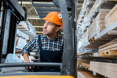 Photo for Attentive warehouse worker in uniform and helmet operating forklift machine - Royalty Free Image