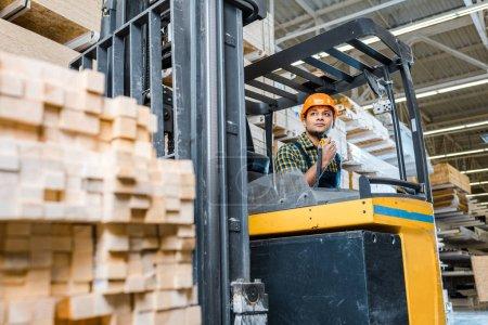 Photo pour Focus sélectif de travailleur d'entrepôt indien assis dans la machine de chariot élévateur - image libre de droit