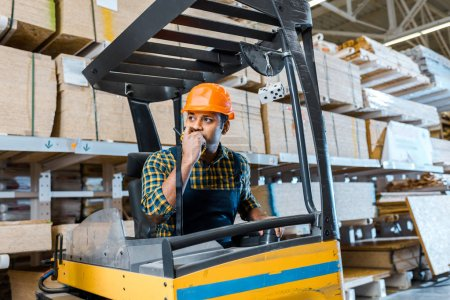Photo for Indian warehouse worker talking on walkie talkie while sitting in forklift machine - Royalty Free Image