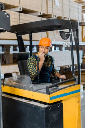 Photo pour Handsome indian warehouse worker sitting in forklift machine and talking on walkie talkie - image libre de droit
