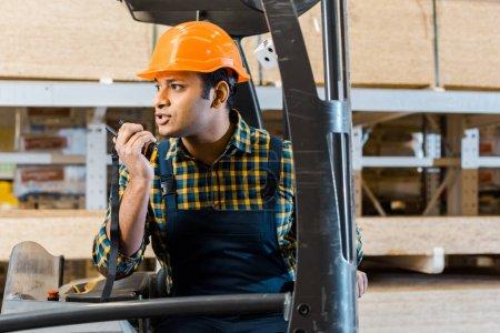 Photo pour Ouvrier indien d'entrepôt dans le casque parlant sur le talkie-walkie tout en étant assis dans la machine de chariot élévateur - image libre de droit