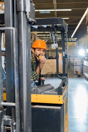 Photo pour Bon-regard ouvrier indien d'entrepôt se reposant dans la machine de chariot élévateur et parlant sur le talkie-walkie - image libre de droit