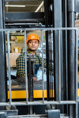 handsome, attentive indian worker sitting in forklift machine in warehouse