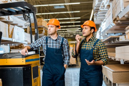 Photo for Multicultural warehouse workers in uniform and helmets standing near forklift machine in storehouse - Royalty Free Image