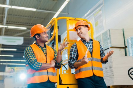 Photo for Cheerful multicultural workers talking and gesturing while standing near scissor lift - Royalty Free Image