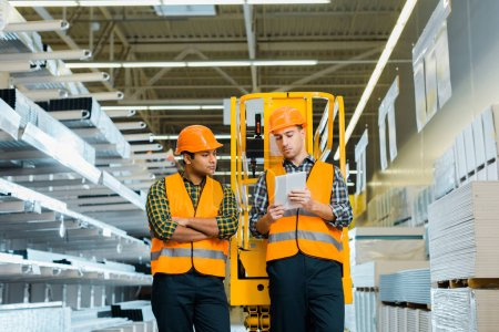 Photo pour Selective focus of concentrated workers using digital laptop in warehouse - image libre de droit