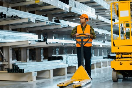 Photo for Handsome indian warehouse worker standing near pallet jack in warehouse - Royalty Free Image