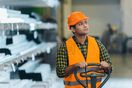 Photo for Handsome indian warehouse worker standing near pallet jack and looking away - Royalty Free Image