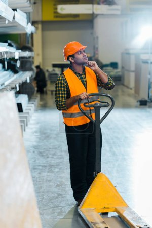 Photo for Thoughtful indian warehouse worker standing near pallet jack and looking away - Royalty Free Image