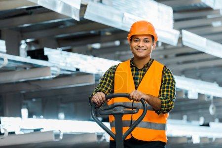 Photo pour Travailleur d'entrepôt indien souriant debout près de palette jack, souriant et regardant la caméra - image libre de droit