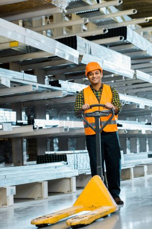 cheerful indian worker standing near pallet jack, smiling and looking at camera