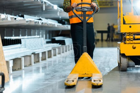 Photo for Partial view of warehouse worker standing with pallet jack near scissor lift - Royalty Free Image