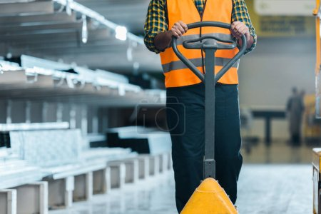 Photo for Cropped view of warehouse worker standing near pallet jack in warehouse - Royalty Free Image