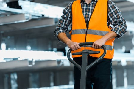 Photo for Partial view of warehouse worker in safety vast standing with pallet jack - Royalty Free Image