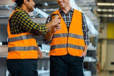 Foto de Alegres trabajadores multiculturales con tazas de papel mientras están de pie en el almacén - Imagen libre de derechos
