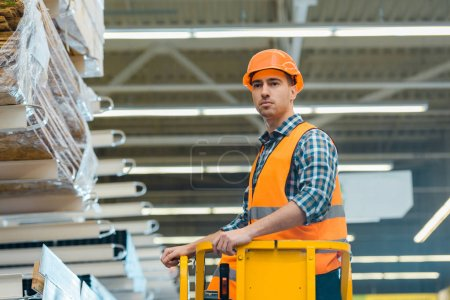 Photo for Handsome, serious worker standing on scissor lift in warehouse - Royalty Free Image