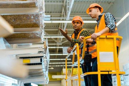 Photo pour Travailleur indien sérieux pointant avec la main à l'étagère avec des matériaux de construction tout en restant sur les ciseaux soulever avec collègue - image libre de droit