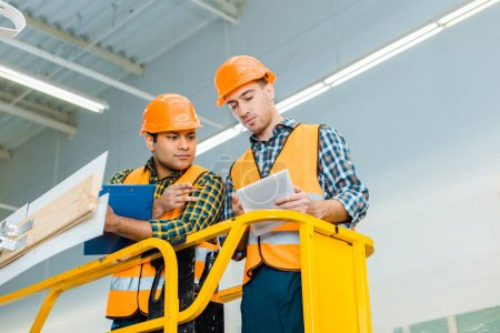 Photo for Thoughtful multicultural workers with digital tablet and clipboard standing on scissor lift - Royalty Free Image
