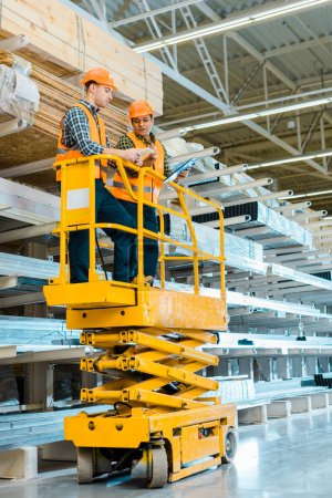Photo for Multicultural warehouse workers with digital tablet and clipboard standing on scissor lift - Royalty Free Image