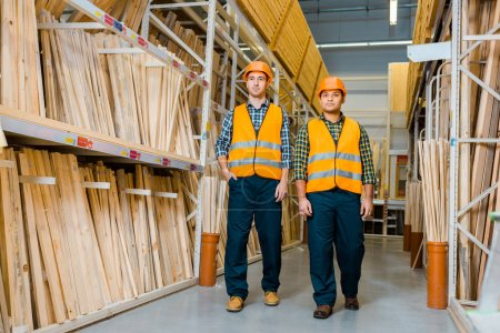multicultural warehouse workers in safety vasts and helmets walking along racks with wooden construction materials