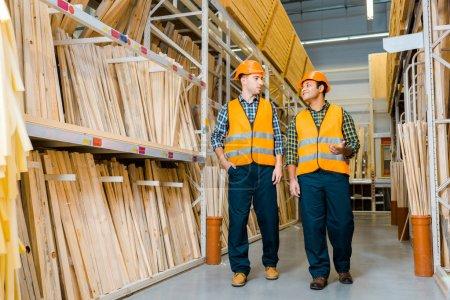 Photo pour Travailleurs multiculturels souriants parler tout en marchant le long des racks avec des matériaux de construction en bois - image libre de droit