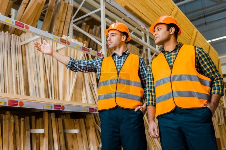 Photo for Handsome multicultural worker pointing with hand at wooden construction materials near indian colleague - Royalty Free Image